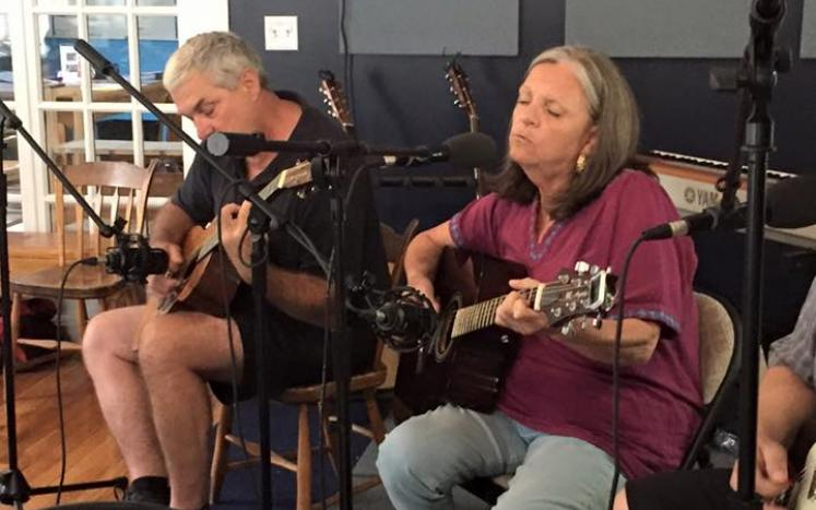 carol pollack female playing guitar with al dimmock male playing guitar